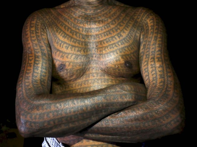 "Mahettar Ram Tandon, 76, a follower of Ramnami Samaj, who has tattooed the name of the Hindu god Ram on his full body, poses for a picture inside his house in the village of Jamgahan, in the eastern state of Chhattisgarh, India, November 17, 2015. ""It was my new birth the day I started having the tattoos,"" Tandon said. ""The old me had died."" ""The young generation just don't feel good about having tattoos on their whole body,"" he added. ""That doesn't mean they don't follow the faith."" REUTERS/Adnan Abidi  PICTURE 9 OF 31 - SEARCH ""RAMNAMI"" FOR ALL IMAGES TPX IMAGES OF THE DAY      - RTX2205I"